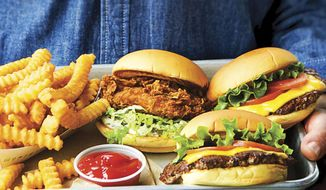 """This image provided by Penguin Random House shows the cover of the book """"Shake Shack: Recipes & Stories."""" The book was co-written by Shake Shack's CEO, Randy Garutti, and culinary director Mark Rosati. (Penguin Random House via AP)"""