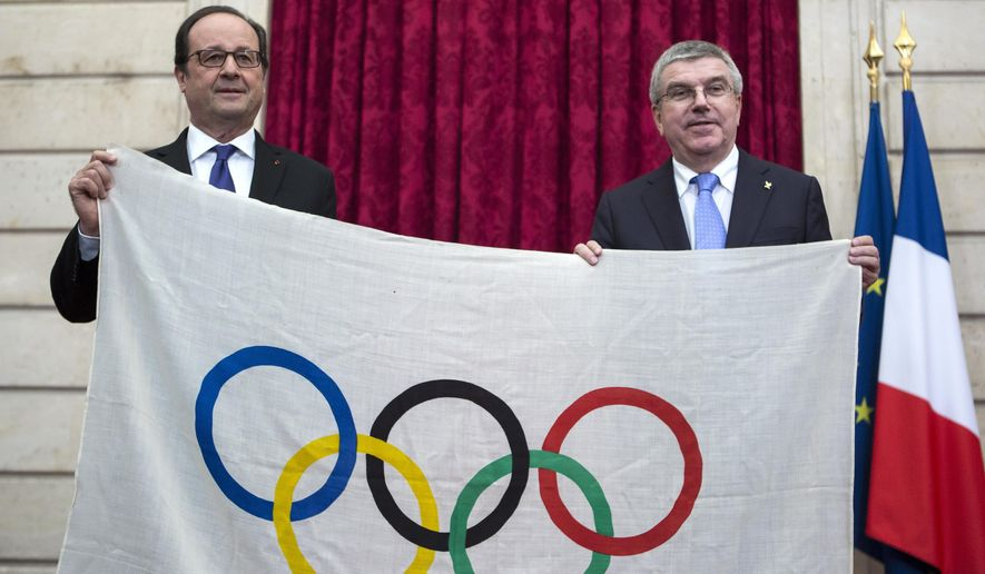 FILE - In this Oct. 2, 2016 file photo, French President Francois Hollande, left, and International Olympic Committee President Thomas Bach, hold a 1924 Olympics games flag during a meeting at the Elysee Palace in Paris. Paris 2024 leaders are confident they have found a strong ally in France's new president Emmanuel Macron. (AP Photo/Kamil Zihnioglu, Pool, File)