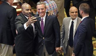 Rep. G. A. Hardaway, D-Memphis, second from left, takes a selfie with Rep. Glen Casada, R-Franklin, after the House adjourned for the year Wednesday, May 10, 2017, in Nashville, Tenn. (AP Photo/Mark Humphrey)