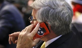 Sen. Todd Gardenhire, R-Chattanooga, talks on a phone with a Tennessee flag cover during a Senate session Wednesday, May 10, 2017, in Nashville, Tenn. (AP Photo/Mark Humphrey)