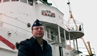 """FILE- In this May 30, 2000, file photo, U.S. Coast Guard Lt. William Moeller of Northford, Conn., poses for a photo in front of the USS Tamaroa. Moeller was aboard the Tamaroa during the 1991 rescue of five Air National Guardsmen who ditched their helicopter as they were trying to rescue the crew of a fishing boat during a fierce storm. The storm and the events surrounding it were recalled in the book """"The Perfect Storm"""" which was made into a motion picture. Officials say they plan to sink the ship Wednesday, May 10, 2017, off the New Jersey and Delaware coasts so it can become part of an artificial reef. (AP Photo/Ed Bailey, File)"""