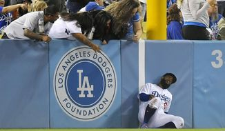 Los Angeles Dodgers left fielder Andrew Toles writhes after running into the left field wall while trying to catch a ball hit for a ground-rule-double by Pittsburgh Pirates' Andrew McCutchen during the seventh inning of a baseball game, Tuesday, May 9, 2017, in Los Angeles. Toles left the game. (AP Photo/Mark J. Terrill)