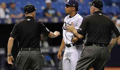 Umpires Mike Everitt, left, and Bill Welke right, separate Tampa Bay Rays pitcher Chris Archer, center, from Kansas City Royals' Salvador Perez after he hit Perez with a pitch during the seventh inning of a baseball game Wednesday, May 10, 2017, in St. Petersburg, Fla. (AP Photo/Steve Nesius)
