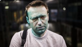 FILE - In this Thursday, April 27, 2017 file photo, Russian opposition leader Alexei Navalny poses for a photo after unknown attackers doused him with green antiseptic outside a conference venue in Moscow, Russia. Russian opposition leader Alexei Navalny wrote on Instagram on Tuesday May 9, 2017 that he has undergone eye surgery in Spain and that doctors expect the vision in his right eye to be restored in several months, after being attacked last month. (Evgeny Feldman/Pool Photo via AP, File)