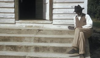 In this 1950's photo released by the National Archives, a man included in a syphilis study sits on steps in front of of a house in Tuskegee, Ala. For 40 years starting in 1932, medical workers in the segregated South withheld treatment for unsuspecting men infected with a sexually transmitted disease simply so doctors could track the ravages of the horrid illness and dissect their bodies afterward. Finally exposed in 1972, the study ended and the men sued, resulting in a $9 million settlement. (National Archive via AP)