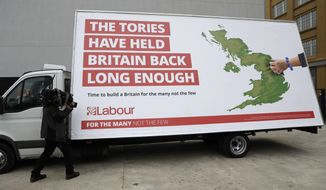 A cameraman films a poster unveiled by Britain's opposition Labour party for the upcoming general election, which their party leader Jeremy Corbyn did not attend, in London, Thursday, May 11, 2017. The British electorate will vote  in a general on June 8. (AP Photo/Matt Dunham)