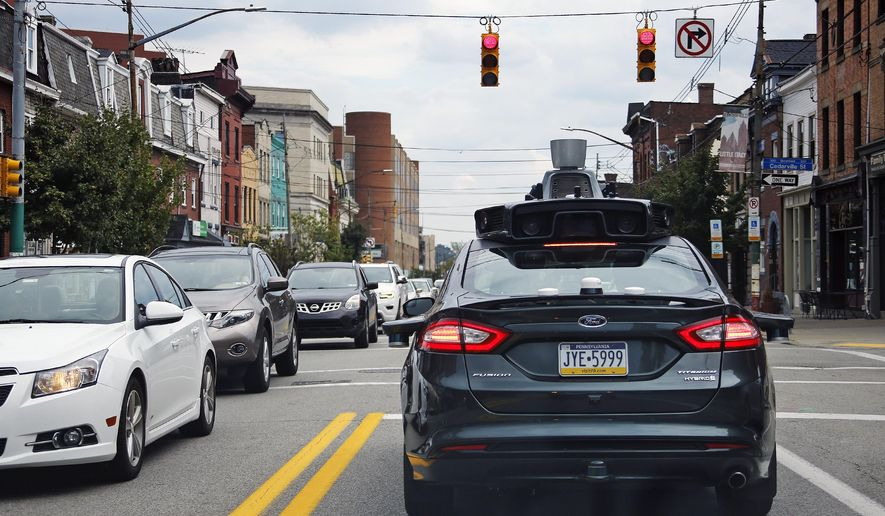 FILE - In this Wednesday, Sept. 14, 2016, file photo, a self-driving Uber car stops at a red light on Liberty Avenue through the Bloomfield neighborhood of Pittsburgh. In just a few years, well-mannered self-driving robotaxis will share the roads with reckless, law-breaking human drivers. The prospect is causing migraines for the people developing the robocars and is slowing their development. But experts say eventually the cars will coexist with human drivers on real roads. (AP Photo/Gene J. Puskar, File)