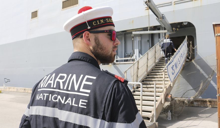 A French sailor stands watch near the FS Mistral, a French amphibious assault ship docked at Naval Base Guam on Thursday, May 11, 2017 near Hagatna, Guam. Military personnel from the United States, Japan, France and the United Kingdom are gathering in the remote U.S. Pacific islands of Guam and Tinian. The exercises come at a time of regional tensions in the South China Sea and North Korea. (AP Photo/Haven Daley)