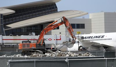 Construction work continues next a Japan Airlines jet at the Tom Bradley International Terminal at Los Angeles International Airport Thursday, May 11, 2017 as the city seeks the 2024 Summer Olympic Games. Envisioning the 2024 Olympic Games in Los Angeles takes imagination. Olympic organizers describe their proposal as ready to go, yet a lot remains on paper or under construction as International Olympic Committee members visit Los Angeles this week. (AP Photo/Reed Saxon)