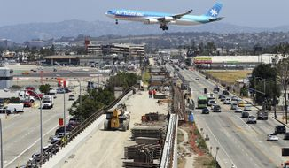 An airliner prepares to land at Los Angeles International Airport over the Metro Crenshaw/LAX Line, en extension of the city's transportation network, Thursday, May 11, 2017 as the city seeks the 2024 Summer Olympic Games. Envisioning the 2024 Olympic Games in Los Angeles takes imagination. Olympic organizers describe their proposal as ready to go, yet a lot remains on paper or under construction as International Olympic Committee members visit Los Angeles this week. (AP Photo/Reed Saxon)
