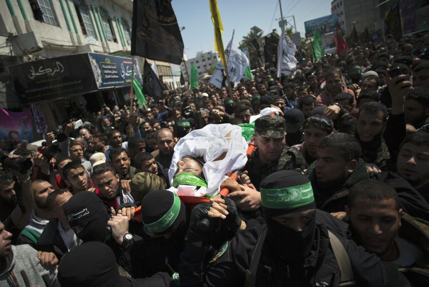 FILE -- In this March, 25, 2017 file photo, gunmen from the Qassam brigade, the militia wing of Hamas, carry the body of Mazen Faqha, a top militant commander, during his funeral in Gaza City. Ismail Haniyeh, Hamas' supreme leader, announced Thursday May 11, 2017, the arrest of a suspect in the shooting death of Faqha in March. Haniyeh refused to identify the suspect, but said that Hamas had determined the gunman, apparently a local Palestinian, had acted on the orders of Israel and he expected the suspect to be executed. (AP Photo/ Khalil Hamra, File)
