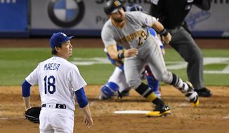 Los Angeles Dodgers starting pitcher Kenta Maeda, left, watches a two-run home run by Pittsburgh Pirates' Francisco Cervelli during the ninth inning of a baseball game, Wednesday, May 10, 2017, in Los Angeles. (AP Photo/Mark J. Terrill)
