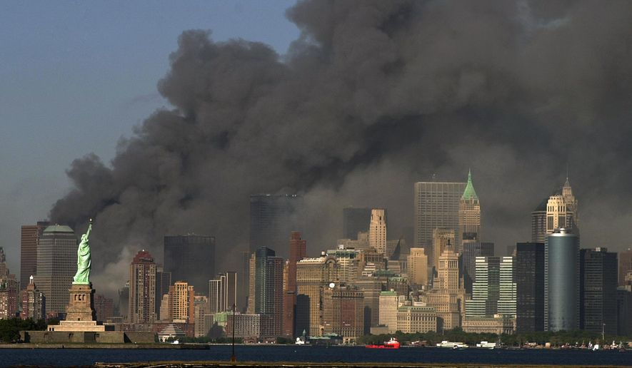 Thick smoke billows into the sky from the area behind the Statue of Liberty where the World Trade Center towers stood on Sept. 11, 2001. (AP Photo/Daniel Hulshizer, File)