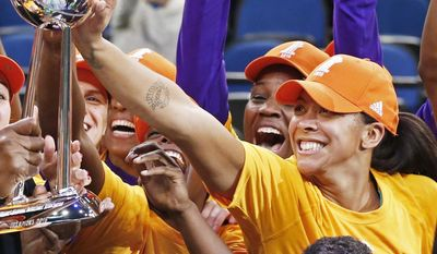 FILE - In this Oct. 20, 2016, file photo, Los Angeles Sparks' Candace Parker, right, touches the trophy after the Sparks won the WNBA championship title with a win over the Minnesota Lynx in Game 5 in Minneapolis. It took Candace Parker nearly a decade to win a WNBA championship. Now the Sparks will try to make sure she's there to enjoy one final celebration of last season's title. The Sparks postponed their ring ceremony a week because Parker, Jantel Lavender and Essence Carson are still playing overseas in the Turkish League finals. (AP Photo/Jim Mone, File)