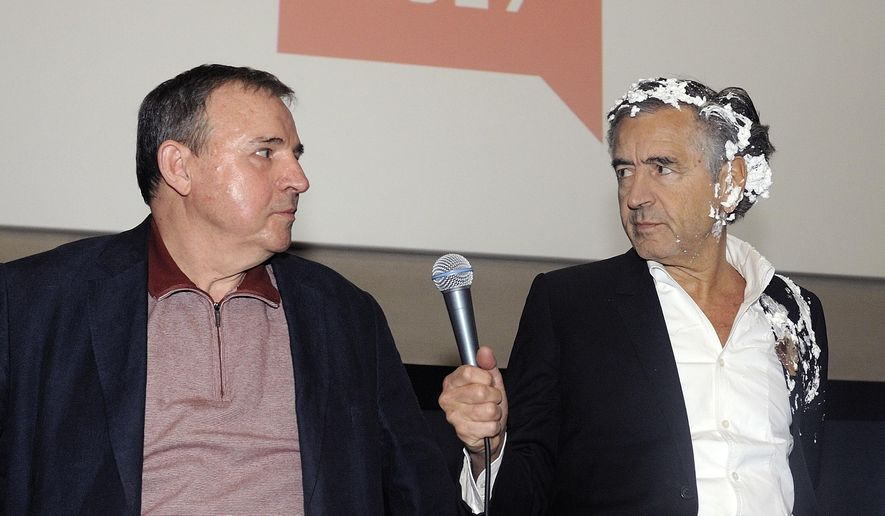 French philosopher and author Bernard-Henri Levy, right, holds a microphone after being struck in the face with a pie by leftist activists during the presentation of his documentary with Serbian movie director Goran Markovic, in Belgrade, Serbia, Wednesday, May 10, 2017. Bernard-Henri Levy, known for his criticism of Serbian nationalist policies during the 1990s Balkan wars, is in Belgrade for the showing of his film about the Kurds' battle against the Islamic State group. (AP Photo)