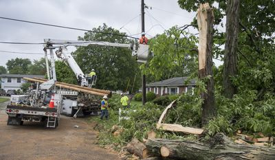 Contractors with Duke Energy work to restore power lines Thursday, May 11, 2017, in Bloomington, Ind., that was damaged by fallen trees from the severe thunderstorm that went through Wednesday night in Bloomington, Ind. (Chris Howell/The Herald-Times via AP)