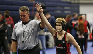FILE - In this Feb. 18, 2017, file photo, Euless Trinity's Mack Beggs is announced as the winner of a semifinal match after Beggs pinned Grand Prairie's Kailyn Clay during the finals of the UIL Region 2-6A wrestling tournament at Allen High School in Allen, Texas. When Texas transgender wrestler Mack Beggs won a girls' state championship, his victory drew jeers and complaints that his steroid therapy treatment had given him an unfair advantage against girls who risked injury just by getting on the mat with him, Now state lawmakers are pushing a bill that could deny Beggs, a Dallas area-junior, a chance to defend his title.  (Nathan Hunsinger/The Dallas Morning News via AP, File)