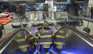 FILE - In this Friday, April 14, 2017, file photo, New York Firefighters make their way to a track at Penn Station in New York. New York Gov. Andrew Cuomo and New Jersey Gov. Chris Christie are calling for a private operator to take over New York's troubled Penn Station, the nation's busiest rail station, they said in a letter to Amtrak CEO Wick Moorman on Thursday, May 11. (AP Photo/Mary Altaffer, File)