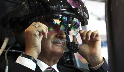 In this Tuesday, May 9, 2017 photo, Turkey's Prime Minister Binali Yildirim, sits at a helicopter gunship, during a visit at IDEF'17, the International Defence Industry Fair in Istanbul, Turkey. Yildirim on Wednesday, May 10, 2017, has spoken out against a U.S. decision to arm Syrian Kurdish fighters which Turkey regard as terrorists, saying it cannot use one terror organization to try and defeat another terror group. (Hakan Goktepe/Prime Minister's Press Service, Pool Photo via AP)