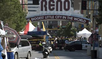 FILE--In this Sunday, July 3, 2016, file photo, Reno police officers cordon off the area after a minivan, left, crashed into a vendor's tent at the Biggest Little City Wing Fest in downtown Reno, Nev. Two Reno police officers have been cleared of any wrongdoing Thursday, May 11, 2017, in the fatal shooting of a California man who drove a mini-van into a chicken wing festival on a crowded downtown street last Fourth of July weekend. (Michael Higdon/The Reno Gazette-Journal via AP, file)