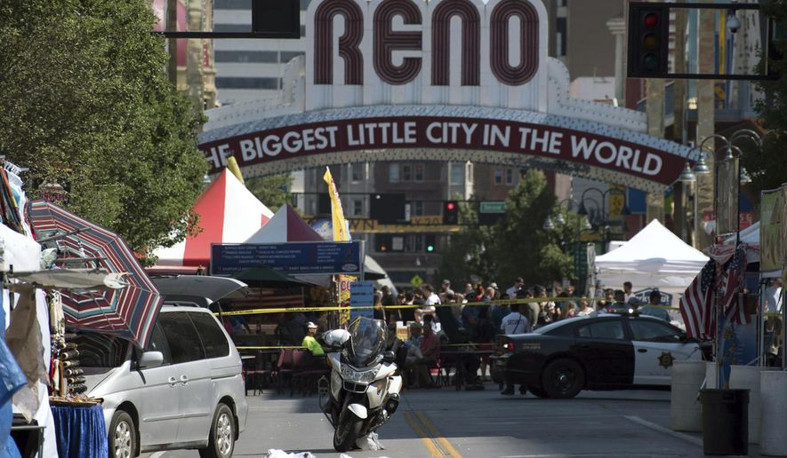 In this Sunday, July 3, 2016, file photo, Reno police officers cordon off the area in downtown Reno, Nev. The city has ordered its bars and nightclubs to close as of 5 p.m. on Friday, March 20, in an effort to combat the ongoing coronavirus outbreak, but casinos will be exempted.  (Michael Higdon/The Reno Gazette-Journal via AP, file) **FILE**