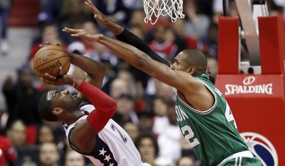 Washington Wizards guard John Wall (2) falls as he shoots against Boston Celtics center Al Horford (42) during the second half of Game 6 of an NBA basketball second-round playoff series, Friday, May 12, 2017, in Washington. The Wizards won 92-91. (AP Photo/Alex Brandon)