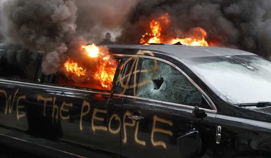 A parked limousine burns during a demonstration after the inauguration of President Donald Trump, Friday, Jan. 20, 2017, in Washington. (AP Photo/John Minchillo) ** FILE **