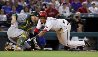 Oakland Athletics catcher Stephen Vogt prepares to turn and attempt the tag as Texas Rangers' Carlos Gomez (14) dives head-first into home, scoring on a Delino DeShields bunt during the fifth inning of a baseball game, Friday, May 12, 2017, in Arlington, Texas. (AP Photo/Tony Gutierrez)