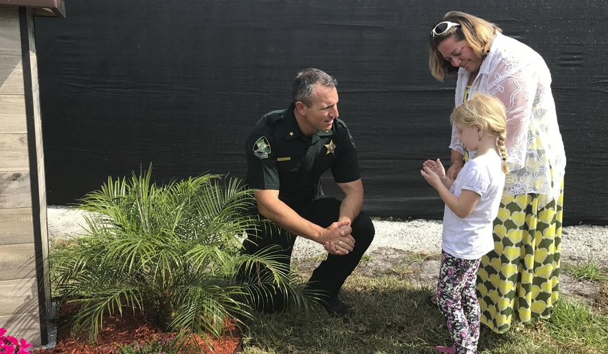 Pasco County Sheriff Chris Nocco speaks with Abigail Kennedy and her daughter, Hannah in Land O'Lakes, Fla., Friday, May 12, 2017. The Adam Kennedy Forensics Field, also known as a body farm, was dedicated and named after Abigail Kennedy's husband, who died in a car crash in January. Dead bodies will be placed in a five-acre patch of land near the Pasco County jail so that researchers can study different facets of decomposition, including how the environment, weather and other factors affect the body.   (AP Photo/Tamara Lush)