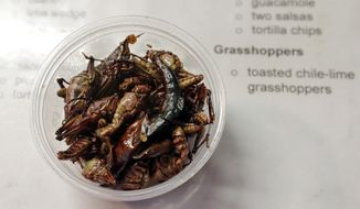 Toasted chile-lime grasshoppers are displayed on a menu at a baseball game between the Seattle Mariners and the Los Angeles Angels Tuesday, May 2, 2017, in Seattle. (AP Photo/Elaine Thompson)