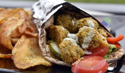 In this May 5, 2017, photo, a falafel sandwich from Harry the Ks Broadcast Bar and Grille at Citizens Bank Park is shown in Philadelphia. This sandwich includes house-made pita, lettuce, English cucumber, bell peppers, tomatoes and sesame mint yogurt sauce. (AP Photo/Derik Hamilton)