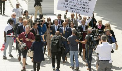 Former Los Angeles County Sheriff Lee Baca, center, with his wife, Carol, walk with attorneys, David Hochman, left, and Nathan Hochman, right, while surrounded by members of the media outside federal court in Los Angeles Friday, May, 12, 2017. Baca was sentenced Friday to three years in prison for obstructing an FBI investigation into abuses at the jails he ran. The 74-year-old Baca, who is in the early stages of Alzheimer's disease, was sentenced by a judge who has shown little leniency when it comes to Baca's role atop a department rife with corruption. (AP Photo/Damian Dovarganes)