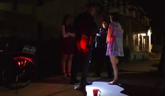 ADVANCE FOR WEEKEND EDITIONS - In this April 22, 2017, photo, Lehigh University Police Officers Patrick McLaughlin, back, and David Fleishman, holding flashlight, write a citation for a Lehigh Student for walking in public with an open container in Allentown, Pa. The red cup had vodka in it. Bethlehem Police and Lehigh University Police were working together patrolling off campus student housing along 5th and Morton Streets in Southside Bethlehem. (April Bartholomew/The Morning Call via AP)