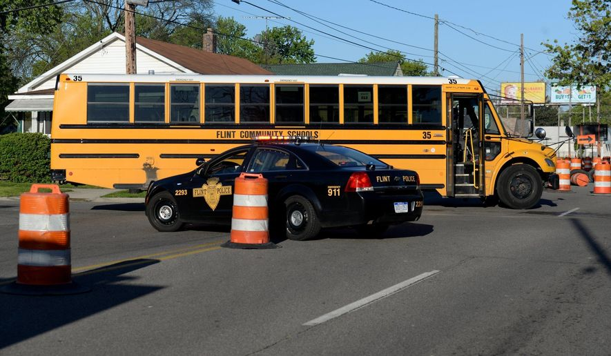 Flint Police work at the scene where a school bus collided with a car, Friday, May 12, 2017, at  the intersection of Atherton Road and Brunswick Avenue in Flint, Mich. (Callaghan O'Hare/Mlive.com/The Flint Journal-MLive.com via AP)