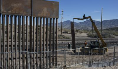 In this  March 30, 2017, file photo, Workers use a crane to lift a segment of a new fence into place on the U.S. side of the border with Mexico, where Sunland Park, New Mexico, meets the Anapra neighborhood of Ciudad Juarez, Mexico, (AP Photo/Rodrigo Abd)