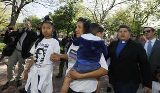 Jeanette Vizguerra, front, a Mexican immigrant who has lived in a church to avoid immigration authorities for the past three months, is surrounded by her family and supporters as she heads to speak after leaving the church early Friday, May 12, 2017, in downtown Denver. Supporters say that Vizguerra has won a two-year deportation delay. (AP Photo/David Zalubowski)