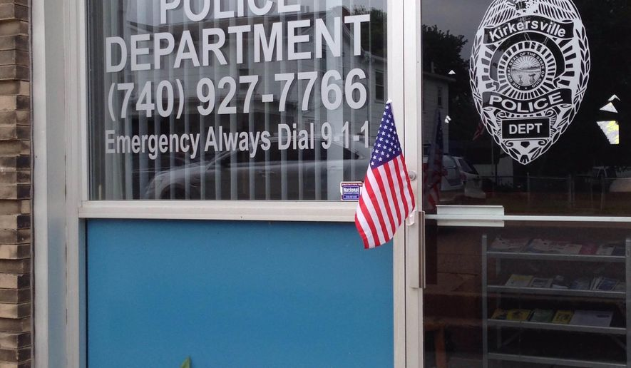 An impromptu memorial of flowers and flags appeared outside the Kirkersville Police Department, on Friday, May, 12, 2017, in Kirkersville, Ohio, after its new chief was shot by an armed gunman. Two workers at nearby Pine Kirk Care Center also were killed. The gunman was found dead inside the center. (AP Photo/Julie Carr Smyth)