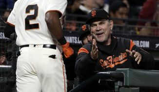 San Francisco Giants manager Bruce Bochy, right, greets Denard Span (2) in the dugout after Span's solo home run against the Cincinnati Reds during the fifth inning of a baseball game Thursday, May 11, 2017, in San Francisco. (AP Photo/Marcio Jose Sanchez)