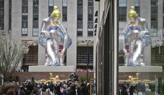 """Seated Ballerina"", center, the public art exhibition of a 45-foot tall inflatable nylon sculpture depicting a seated ballerina from artist Jeff Koons' Antiquity series, is displayed at Rockefeller Center after it was unveiled Friday May 12, 2017, in New York. (AP Photo/Bebeto Matthews)."