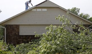 A roofer from Dunnwright Roofing works on a roof after it was damaged in a storm in Owasso, Okla., on Thursday, May 11, 2017. The National Weather Service said a tornado touched down in the Tulsa suburb of Owasso Thursday and a possible tornado struck near Perkins, about 45 miles northeast of Oklahoma City.Damage was reported to roofs and trees, but there are no reports of injuries. (Ian Maule/Tulsa World via AP)