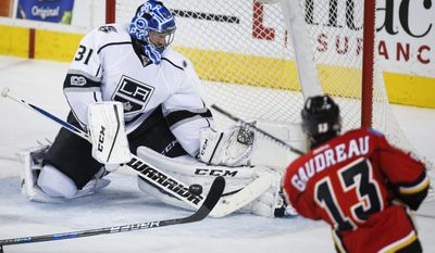 FILE - In this Feb. 28, 2017, file photo, Los Angeles Kings goalie Ben Bishop, left, stops a shot from Calgary Flames' Johnny Gaudreau during second period NHL hockey action in Calgary, Alberta. The Dallas Stars have signed Bishop to a six-year, $29.5-million deal. General manager Jim Nill announced the terms Friday, May 12, 2017, less than a week after acquiring rights to the 30-year-old Bishop from the Los Angeles Kings for a fourth-round pick in next month's draft. The 6-foot-7 Bishop played just seven games after the Kings acquired him from Tampa Bay.  (Jeff McIntosh/The Canadian Press via AP, File)