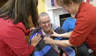 In this April 26, 2017, photo, Gale Grover, left, and Joleene Kooyman give a Quilt of Valor to Willis Burton, who served in World War II, at Cache Valley Assisted Living in Providence, Utah. (Eli Lucero/The Herald Journal via AP)