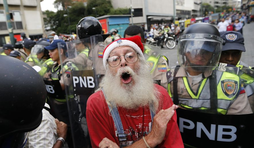 A man derides police blocking a march of older Venezuelans from reaching the Ombudsman's Office in protest of President Nicolas Maduro in Caracas, Venezuela, Friday, May 12, 2017. The anti-government protest movement, that has drawn masses of people into the streets nearly every day since March, has left some three dozen dead. (AP Photo/Ariana Cubillos)