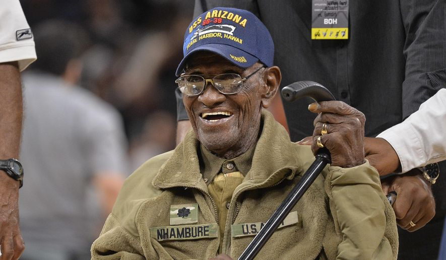 In this March 23, 2017, file photo, Richard Overton leaves the court after a special presentation honoring him as the oldest living American war veteran, during a timeout in an NBA basketball game between the Memphis Grizzlies and the San Antonio Spurs. Overton was honored by his hometown of Austin, Texas, on his 111th birthday on May 11, 2017. (AP Photo/Darren Abate, File)