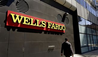 FILE - In this July 14, 2014 file photo, a man passes by a Wells Fargo bank office in Oakland, Calif. Lawyers suing Wells Fargo on behalf of aggrieved customers say in court filing late Thursday, May 11, 2017, the bank may have opened about 3.5 million unauthorized accounts, far more than the figure bank and regulators disclosed last year. (AP Photo/Ben Margot, File)