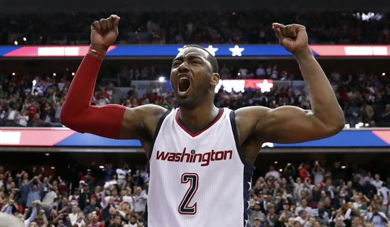 Washington Wizards guard John Wall celebrates as he stands on the scorer's table after Game 6 against the Boston Celtics in an NBA basketball second-round playoff series, Friday, May 12, 2017, in Washington. Wall sank the game-winning 3-point shot. The Wizards won 92-91. (AP Photo/Alex Brandon)