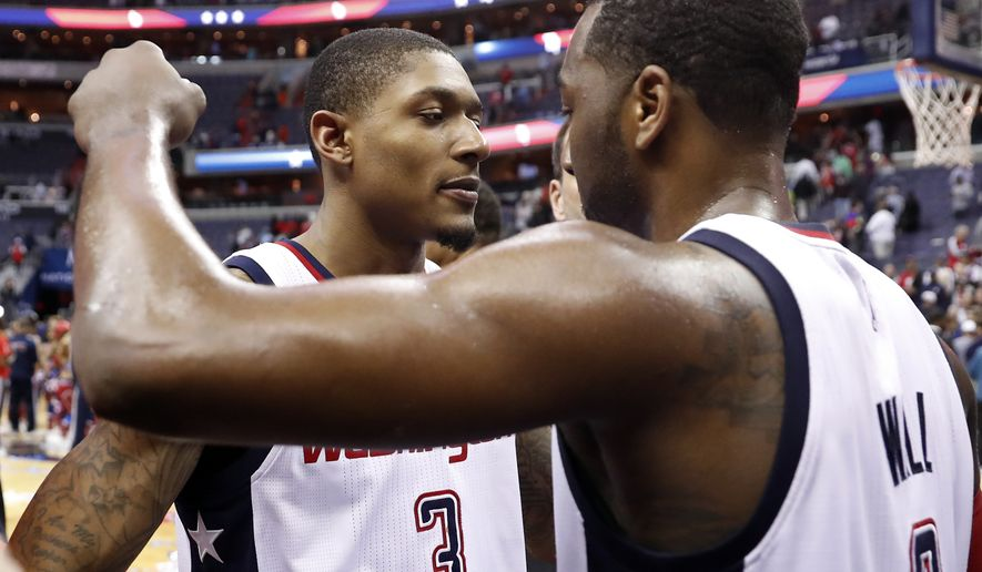 Washington Wizards guard Bradley Beal (3) and Washington Wizards guard John Wall (2) embrace after game 6 of the Eastern Conference semifinal NBA basketball playoff series against the Boston Celtics, Friday, May 12, 2017, in Washington. The Wizards won 92-91. (AP Photo/Alex Brandon)