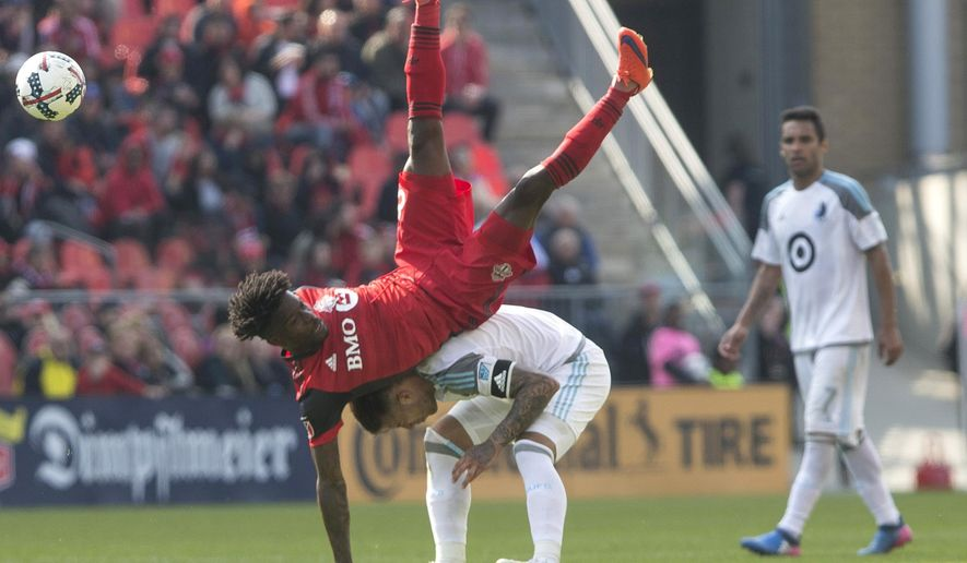 Toronto FC Tosaint Ricketts, top,  is upended as he challenges for the ball with Minnesota United FC's Francisco Calvo during the second half of an MLS game in Toronto on Saturday, May 13, 2017. (Chris Young/The Canadian Press via AP)
