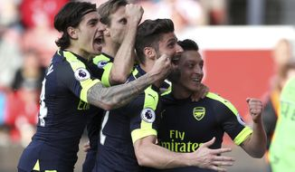 Arsenal's Mesut Ozil, right, celebrates scoring his side's second goal of the game with teammates during their English Premier League soccer match against Stoke City at the bet365 Stadium, Stoke-on-Trent, England, Saturday, May 13, 2017. (Nick Potts/PA via AP)