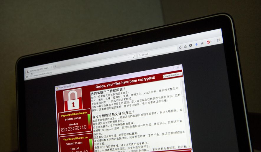 A screenshot of the warning screen from a purported ransomware attack, as captured by a computer user in Taiwan, is seen on laptop in Beijing, Saturday, May 13, 2017. Dozens of countries were hit with a huge cyberextortion attack Friday that locked up computers and held users' files for ransom at a multitude of hospitals, companies and government agencies. (AP Photo/Mark Schiefelbein) **FILE**